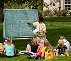 Aba Mbirika (PhD, 2010) holding class outdoors on a pleasant day on the UI Pentacrest