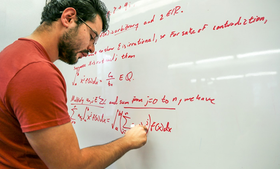 Mathematics Graduate student writing on the board